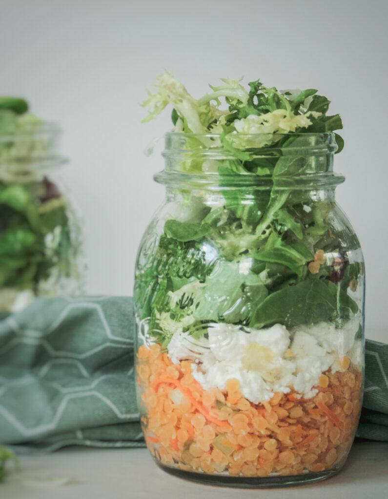 Dieser Linsensalat im Glas ist in nur 20 Minuten vorbereitet und schmeckt dank Feta und Pflücksalat frisch, aromatisch und ist eine richtige Eiweißbombe fürs Büro oder als Abendessen.